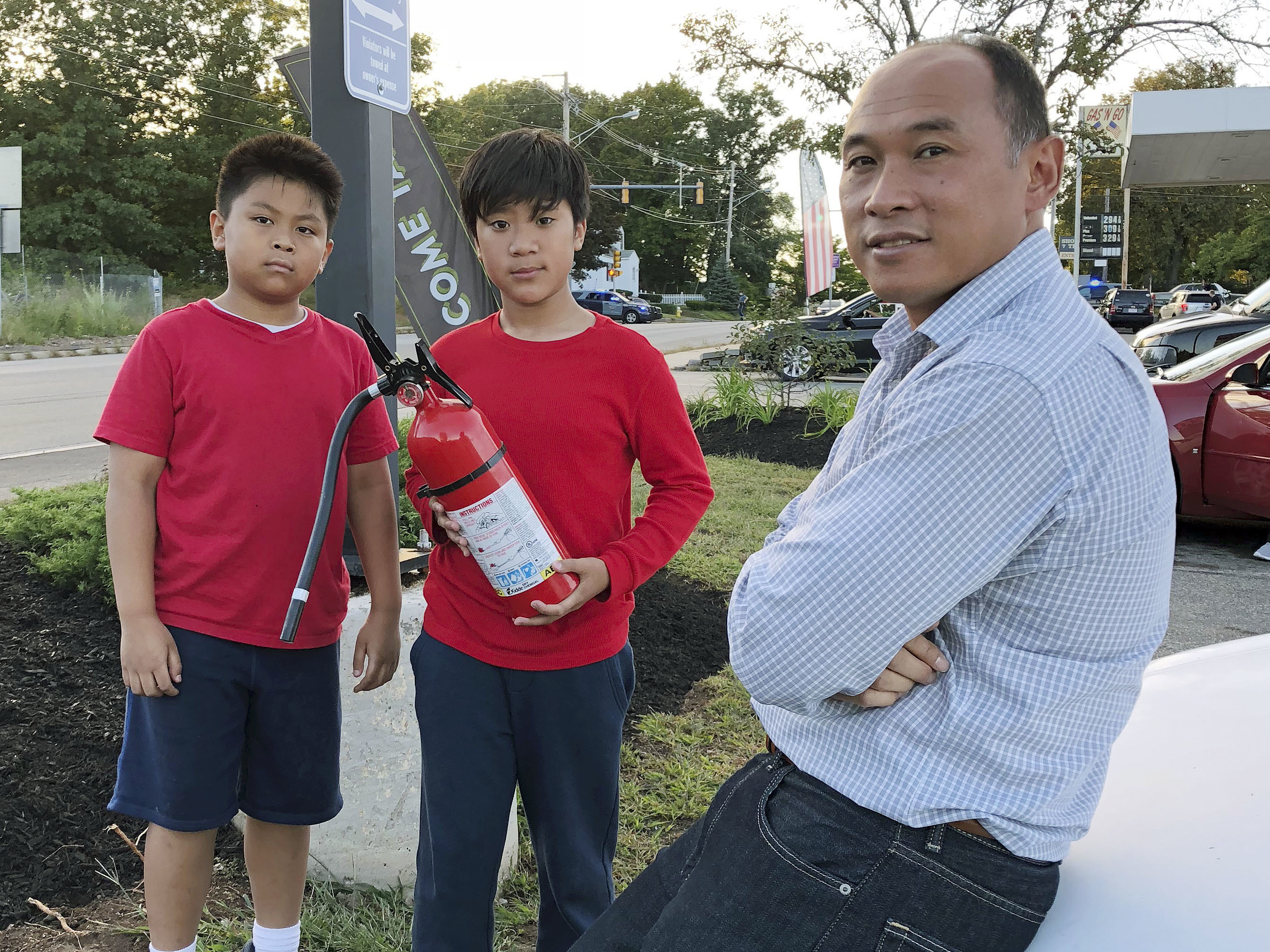 Ra Nam (right), with his sons Evan (left) and Tristan (center), wait in a parking lot outside their Colonial Heights neighborhood in Lawrence, Mass., which was evacuated Thursday because of the fires and explosions.
