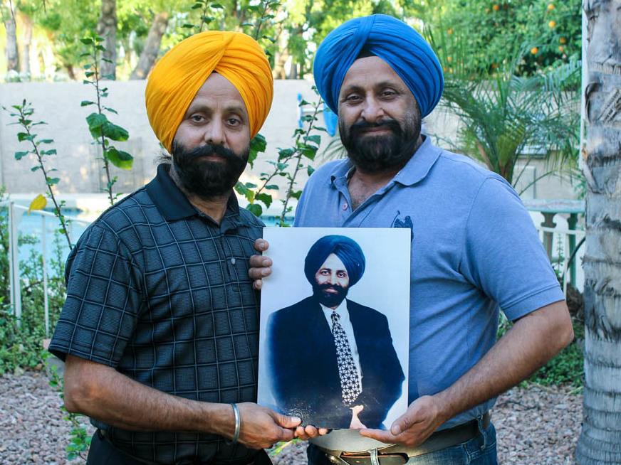 Rana Sodhi (L) and Harjit Sodhi hold a photograph of their late brother, Balbir Singh Sodhi, who was shot and killed at 52. Since his death, the brothers have been involved in educating others about Sikhism and the discrimination their community faces in the U.S.