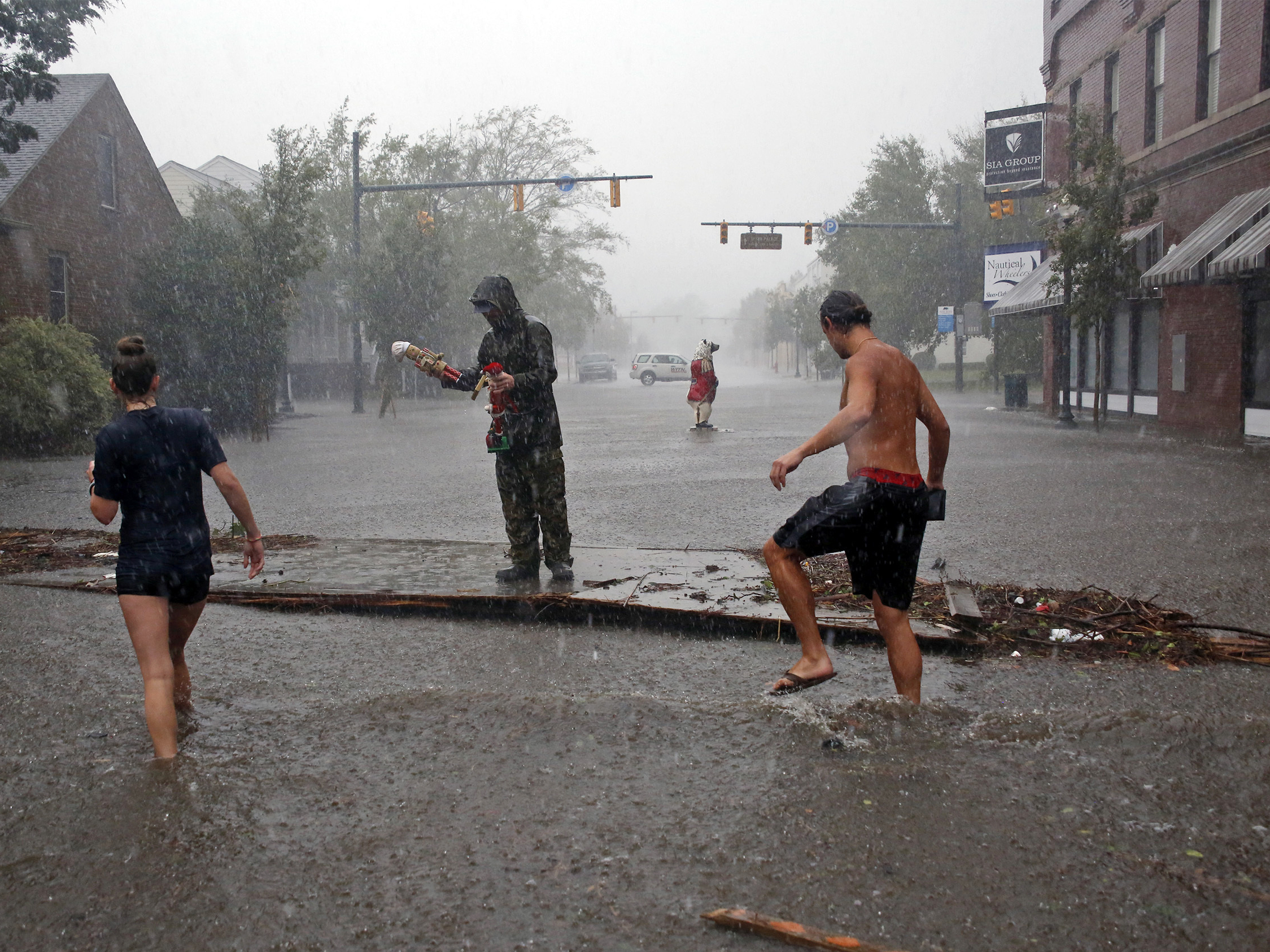People survey damage and flooding brought by Hurricane Florence to Front Street in downtown New Bern N.C. Friday