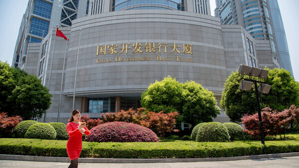 A woman walks in front of the China Development Bank tower in the Pudong district of Shanghai in 2015. That and the Export-Import Bank of China have provided nearly $1 trillion in financing to foreign governments since the early 2000s.