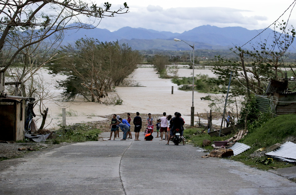 Residents stand by a flooded road following the onslaught of Typhoon Mangkhut in Tuguegarao city in Cagayan province, northeastern Philippines, on Sept. 15.