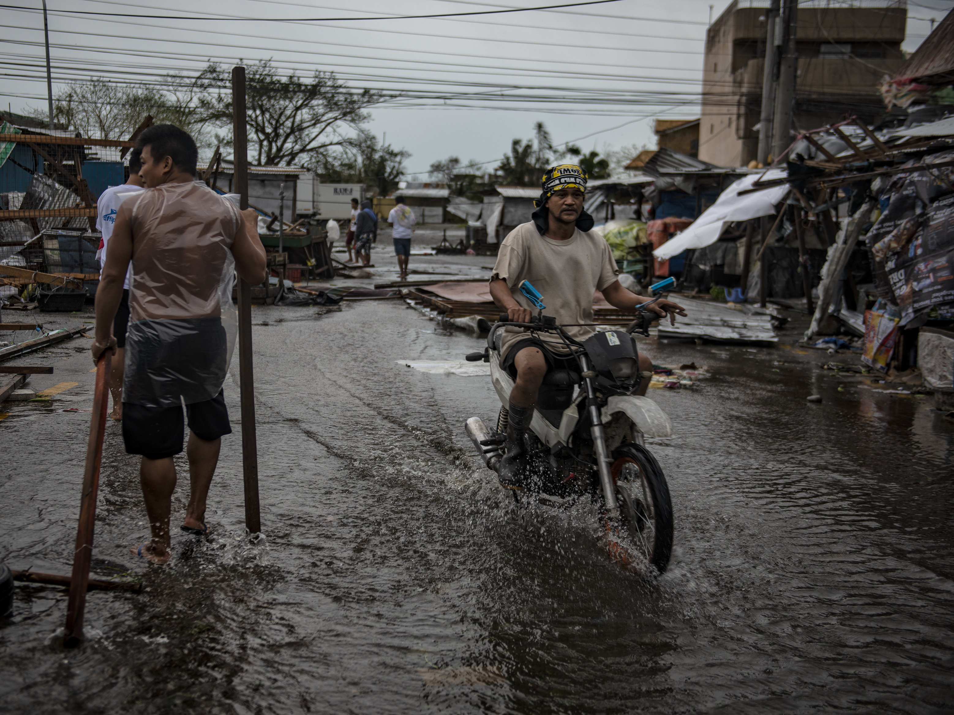 Residents walk on flooded streets as typhoon Mangkhut batters their city on Sept. 15 in Tuguegarao, Philippines. Typhoon Mangkhut hammered northern Philippines as it made landfall Saturday morning leaving at least 12 people dead.
