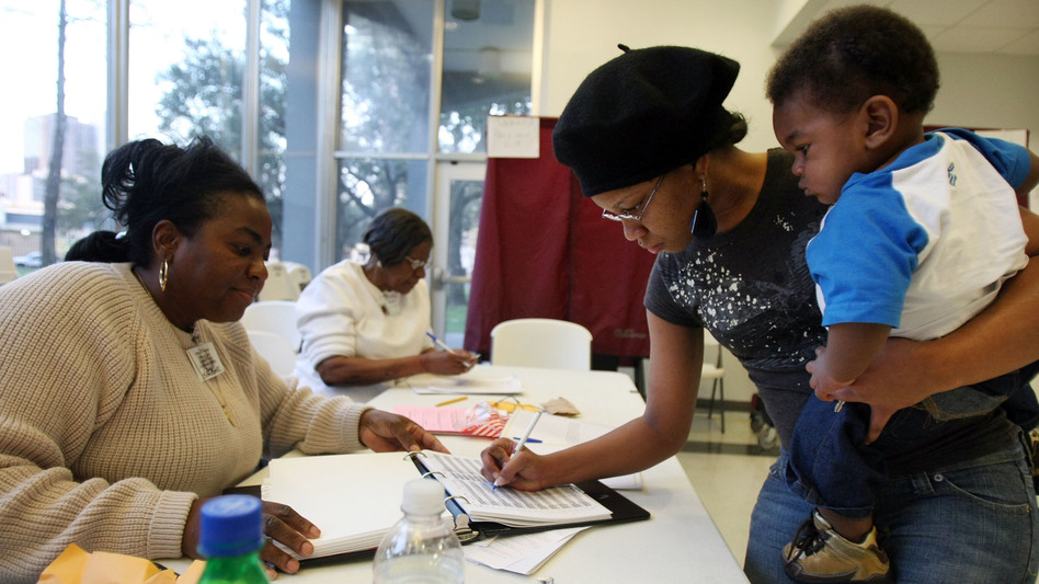 Charnisha Thomas signs in during the Louisiana presidential primary in 2008. In a new poll released Monday, African-American voters say they wait in longer lines and travel farther to get to polling places than white voters. (Mario Tama/Getty Images)