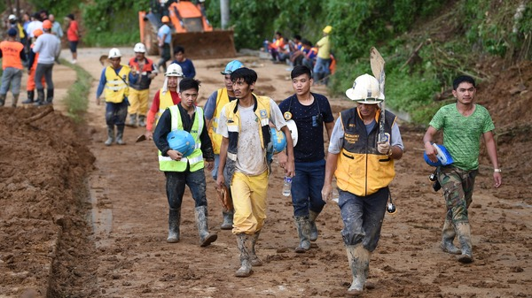 Volunteer rescuers head home after working to dig out victims of a landslide triggered by heavy rains from Typhoon Mangkhut in the Philippine