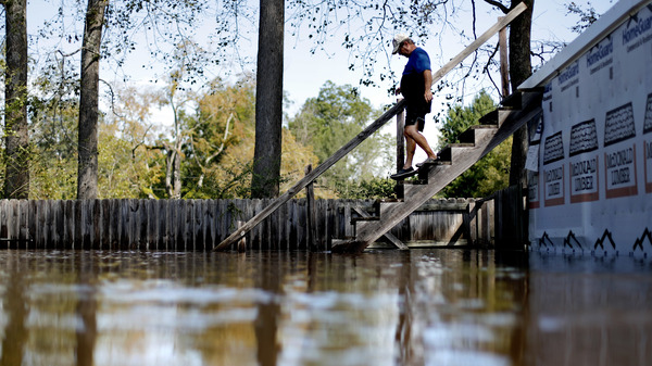 Kenny Babb walks down a staircase on his flooded property as the Little River continues to rise in the aftermath of Hurricane Florence. Coastal residents may have to accept floods as part of life.
