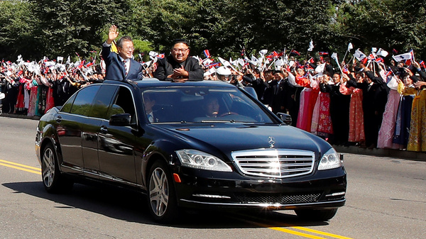 South Korean President Moon Jae-in and North Korean leader Kim Jong Un stand and wave in an open-air Mercedes-Benz as thousands of people welcome their motorcade in Pyongyang.