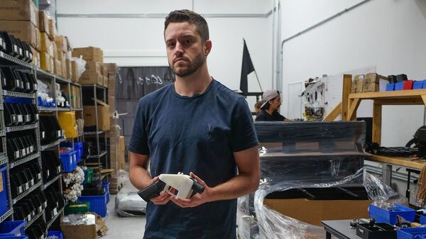 """Cody Wilson, owner of Defense Distributed, holds a 3D printed gun, called the """"Liberator,"""" in his factory in Austin, Texas, on August. The 30-year-old has been accused of sexual assault of a minor."""