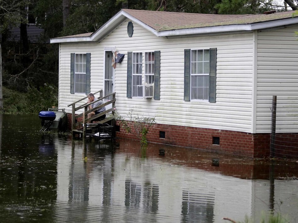 A North Carolina resident sits on his staircase earlier this week, staring into the water that surrounded his home after Florence hit Emerald Isle, N.C. (Tom Copeland/AP)