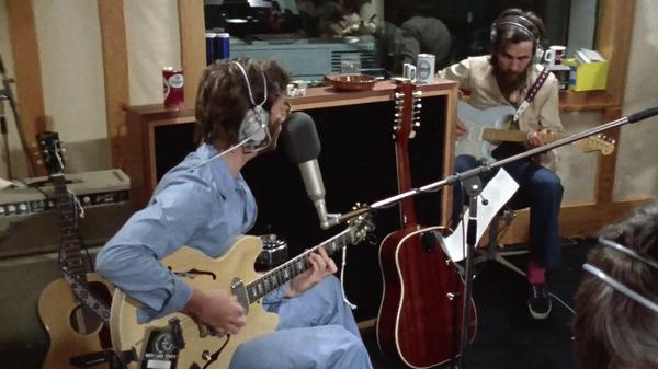 John Lennon and George Harrison in studio, recording Lennon
