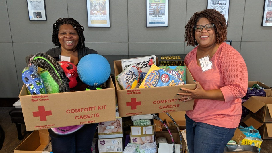 Krista Holland (right) and Regina Wooten, another Wilmington principal, pose with toys Holland brought to a Chapel Hill shelter. (Lisa Philip/WUNC)