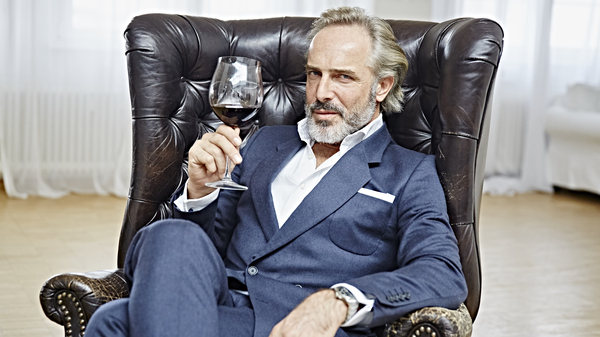 Portrait of a Man with Full Beard sitting in an Armchair holding a Glass of Wine