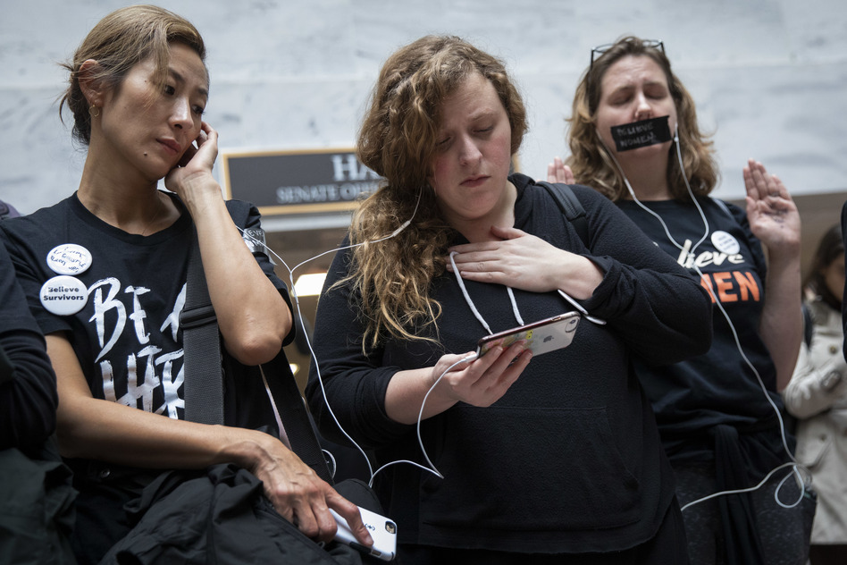 Protesters rallying against Kavanaugh watch testimony from Ford on a smartphone inside the Hart Senate Office Building in Washington, D.C. (Drew Angerer/Getty Images)