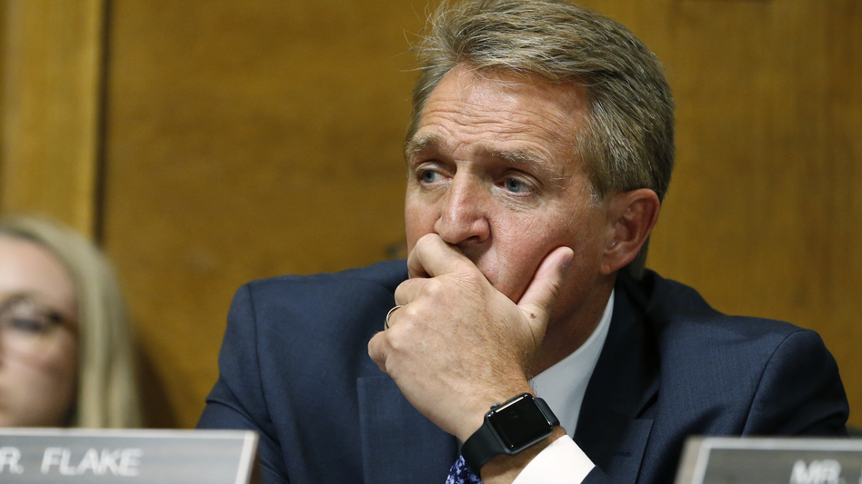 Sen. Jeff Flake, R-Ariz., listens as Christine Blasey Ford testifies before the Senate Judiciary Committee on Thursday. (Michael Reynolds/AP)