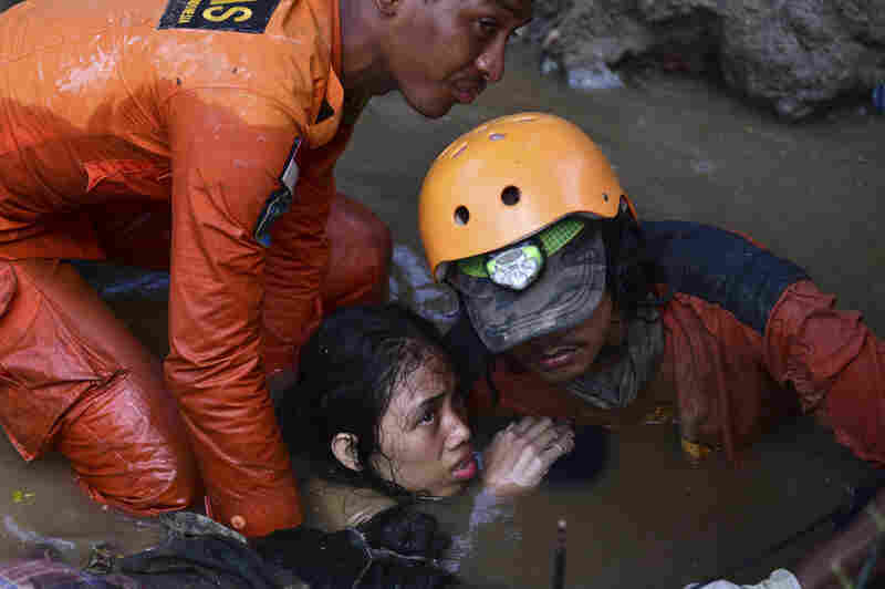 Rescuers help 15-year-old earthquake victim Nurul Istikharah escape floodwater in her damaged house following earthquakes and a tsunami in Palu, central Sulawesi, Indonesia, on Sunday.