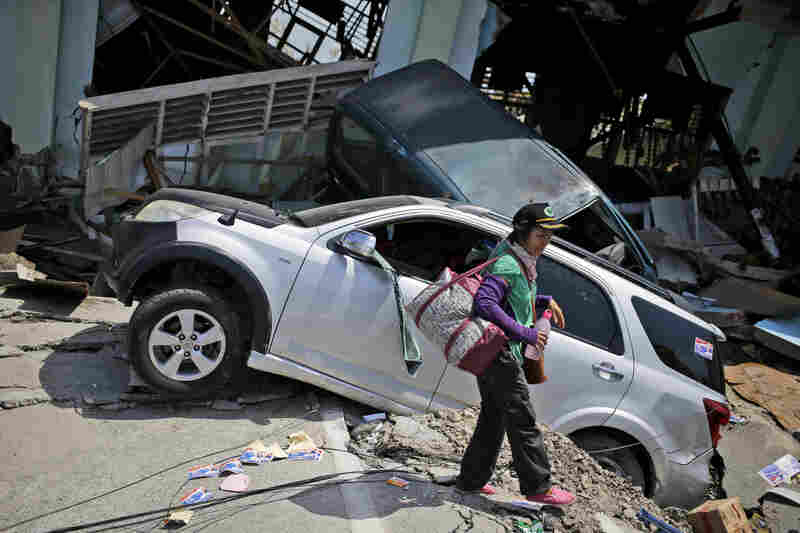 A woman walks past wrecked cars in Palu's Balaroa neighborhood, which was hit hard by the quake and tsunami.