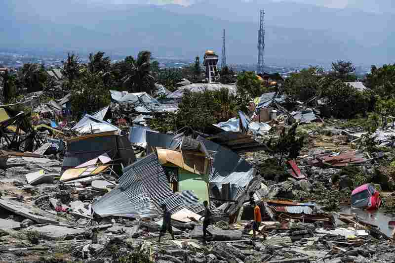 Residents walk past destroyed buildings in the Perumnas Balaroa village of Palu. The bodies of dozens of students were pulled from their landslide-swamped church nearby.