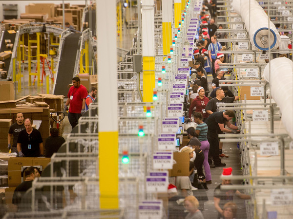 Amazon says it will pay all its U.S. workers at least $15 an hour. Here, workers prepare shipments at an Amazon Fulfillment Center in California during the early Christmas rush in 2014.