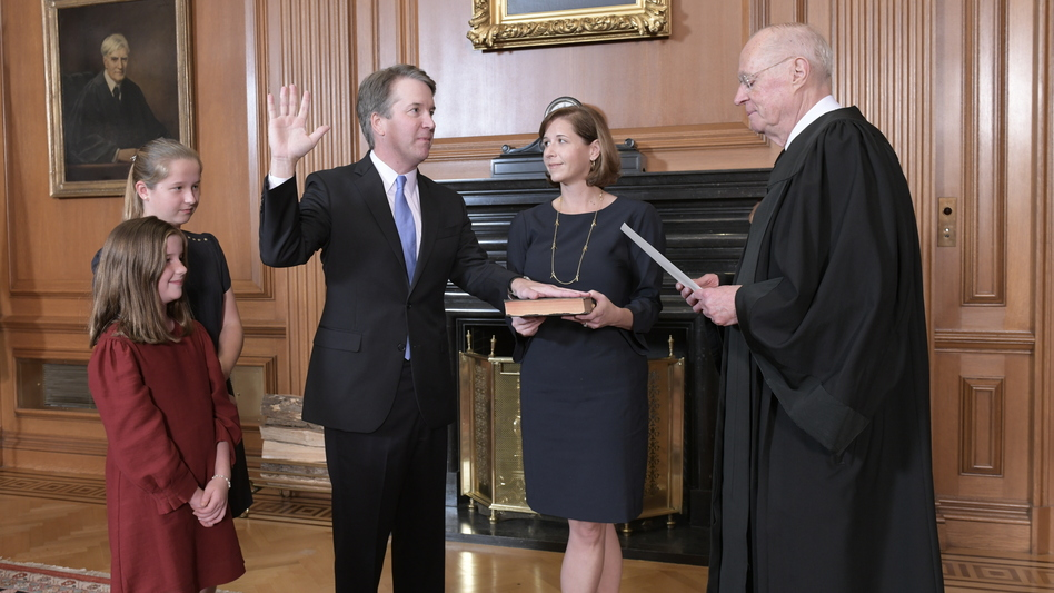 Retired Justice Anthony Kennedy administers the Judicial Oath to Judge Brett Kavanaugh in the Justices' Conference Room of the Supreme Court Building. Ashley Kavanaugh holds the Bible. At left are their daughters, Margaret, background, and Liza. (Fred Schilling/Collection of the Supreme Court of the United States via AP)