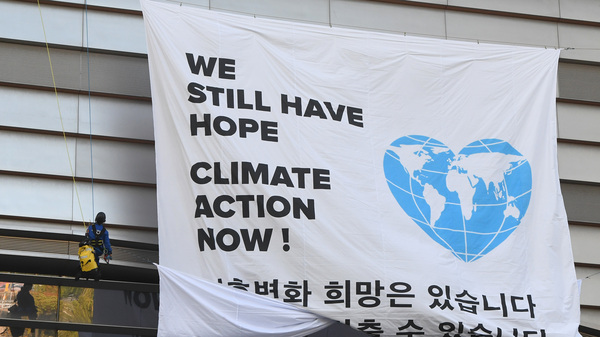 Greenpeace activists hang a banner prior to a press conference of the Intergovernmental Panel for Climate Change (IPCC) in Incheon, South Korea. The landmark U.N. report on limiting global warming to 1.5 degrees Celsius was released after a week-long meeting of the IPCC