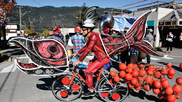 Vancouver activist and community food developer Ian Marcuse rides a bike outfitted like a spawning salmon created by artist Tamara Unroe.