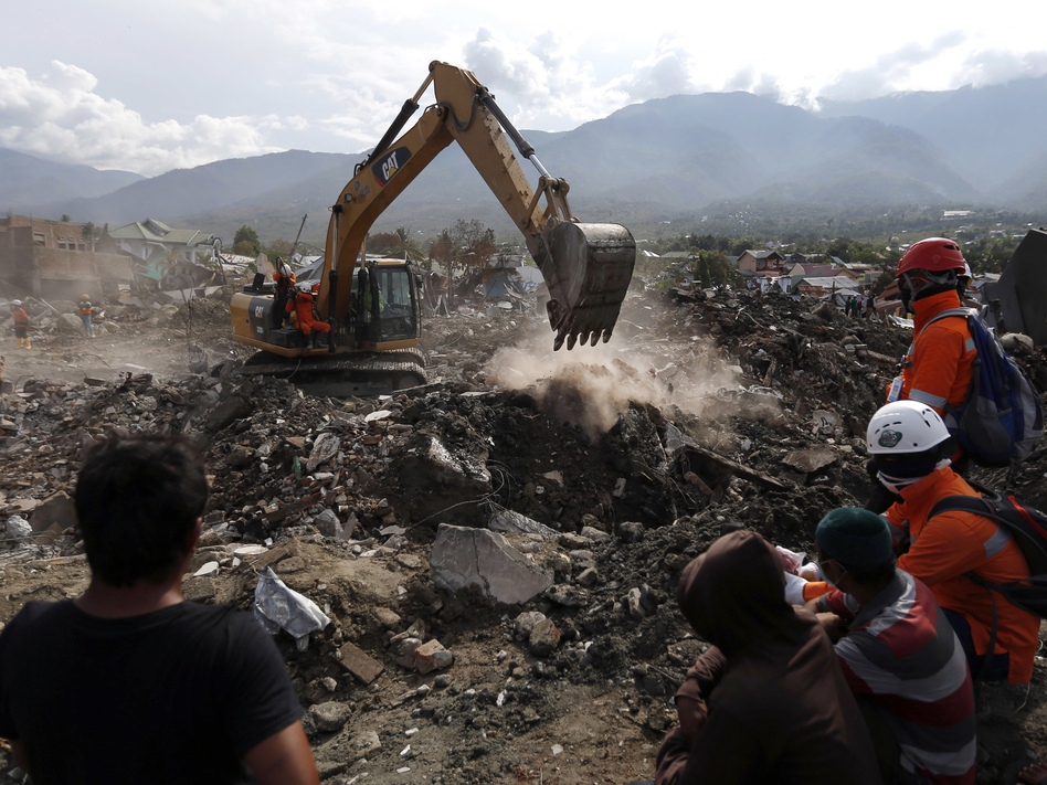 Rescue workers watch as a heavy machine dig through rubble searching for earthquake victims on Thursday in Palu, Central Sulawesi, Indonesia.