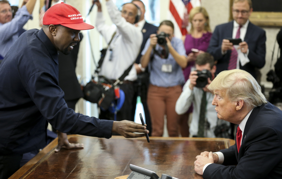 Rapper Kanye West shows a picture of a plane on a phone to President Trump during a meeting in the Oval Office on Thursday.