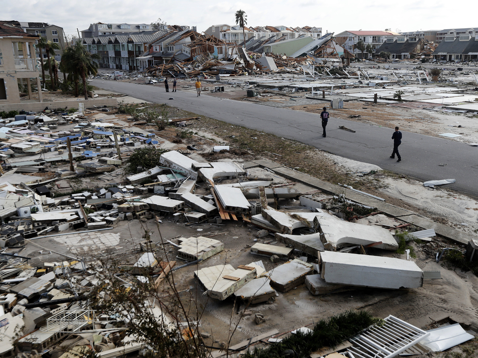 Rescue personnel walk through debris in Mexico Beach, which was devastated by Hurricane Michael.