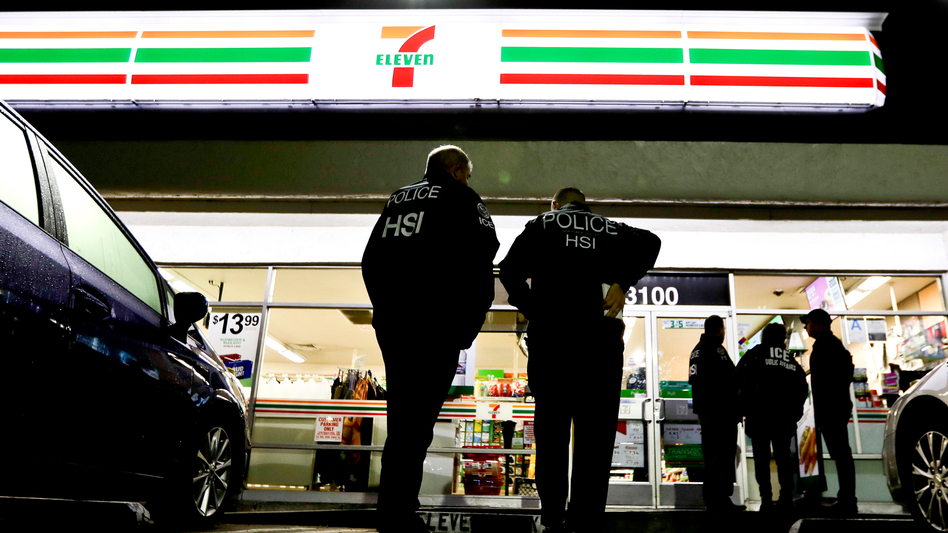 U.S. Immigration and Customs Enforcement agents serve an employment audit notice at a 7-Eleven convenience store in Los Angeles. California is divided over the state's new sanctuary law, which took effect earlier this year. (Chris Carlson/AP)