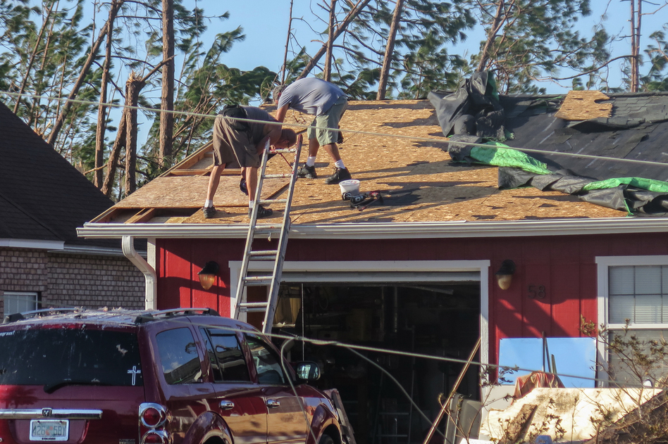 Lance Erwin works with a neighbor in Mexico Beach, Fla., to repair parts of his roof after it was blown off by Hurricane Michael. Rules are looser in the Pandhandle, allowing construction that couldn't stand up to the storm's 155 mph winds. (Greg Allen/NPR)