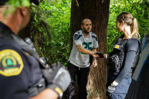 Social worker Lauren Rainbow (right) meets a man illegally camped in the woods in Snohomish County. A new program in the county helps people with addiction, instead of arresting them.