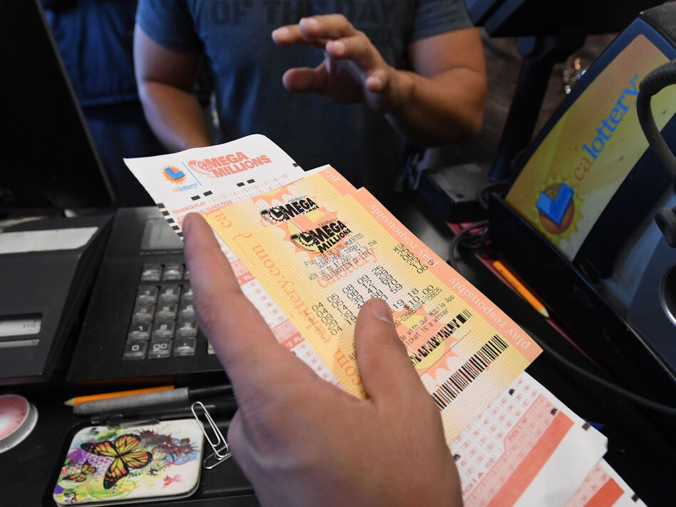 A man in Torrance, Calif., buys a Mega Millions ticket hours before the drawing on Friday evening. No one won that drawing, and the jackpot went up to $1.6 billion. (Mark Ralston/AFP/Getty Images)