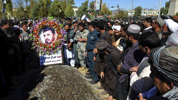 Mourners stand beside the grave of Gen. Abdul Raziq, the Kandahar police chief who was killed by a Taliban attack, during his burial ceremony Friday in Kandahar, Afghanistan. U.S. Army Brig. Gen. Jeffrey Smiley was wounded in the attack.