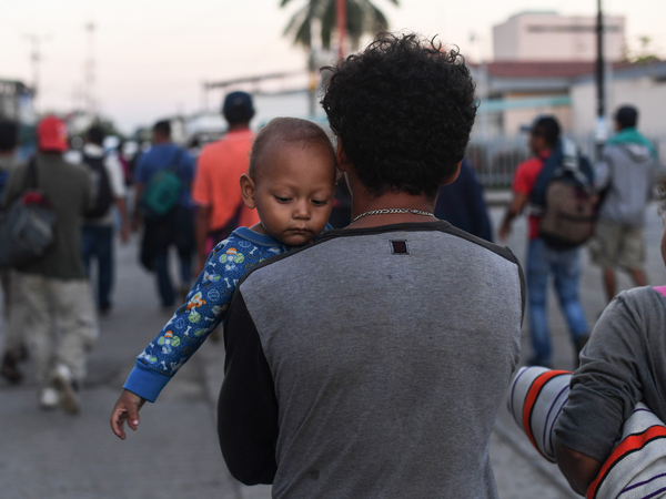 A migrant in a caravan bound for the United States carries a baby in Ciudad Hidalgo, Mexico, on Monday.