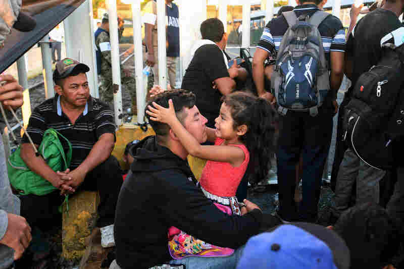 A Honduran migrant and his daughter rest as they wait to cross the border from Guatemala into Mexico on Monday