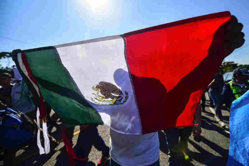 A Central American migrant holds a Mexican national flag during the trek from Ciudad Hidalgo to Tapachula on Sunday.