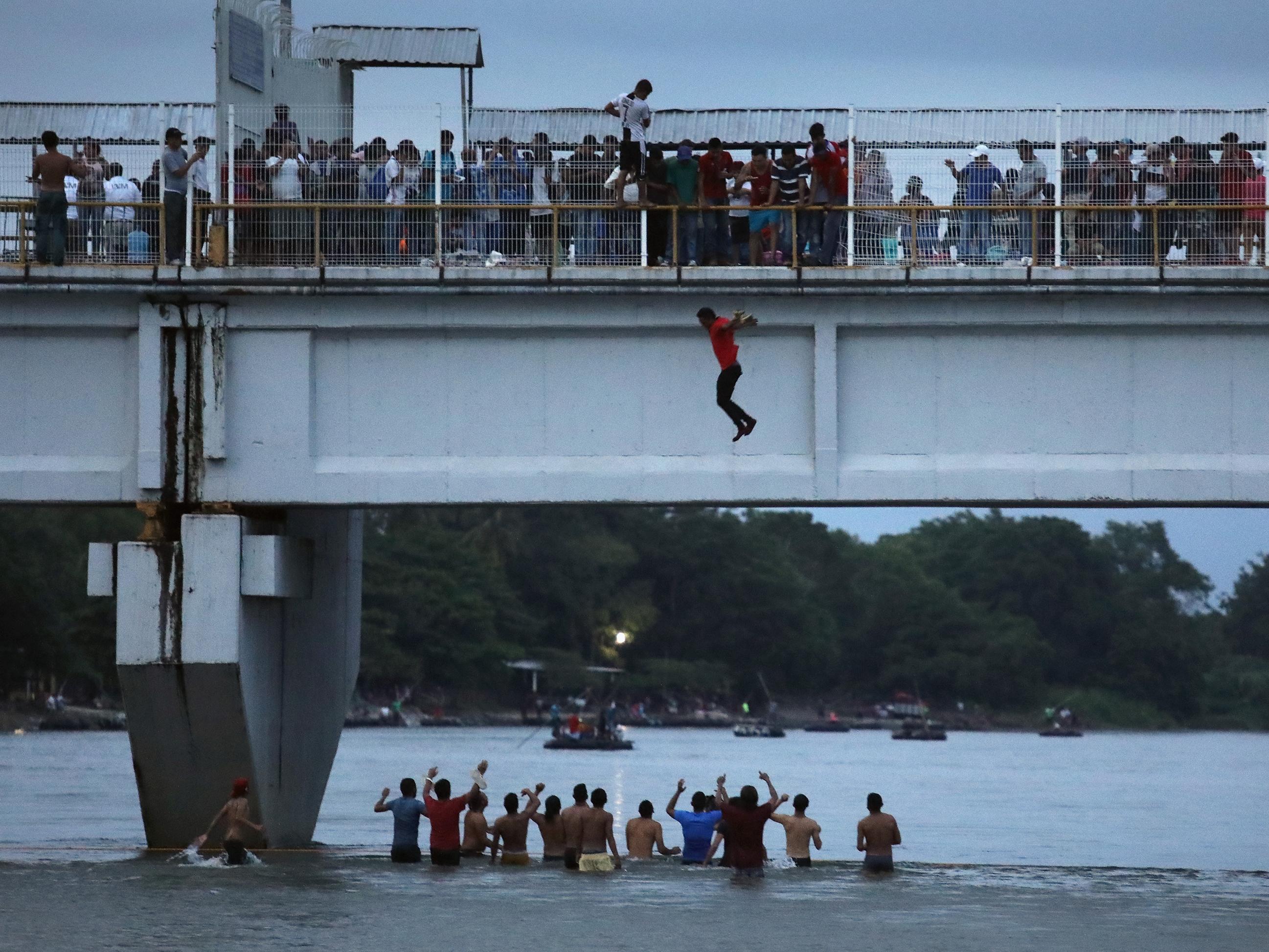 An migrant jumps off a bridge to enter Ciudad Hidalgo, Mexico, from Guatemala on Saturday.