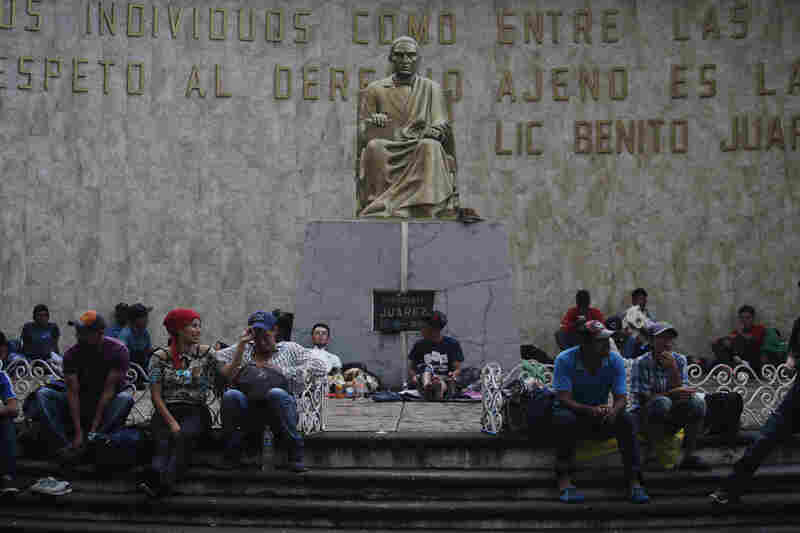 Central American migrants rest Sunday in Tapachula under a statue of Benito Juarez, a Mexican national hero and former president.