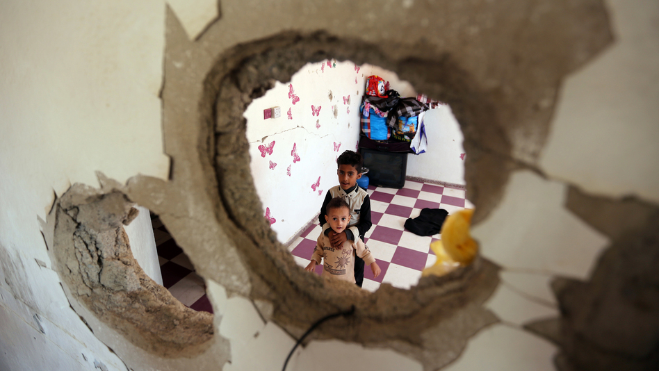 Displaced Yemeni children stare through a hole in the wall of a half-destroyed house in Taez, where they have been staying with several families since violence drove them from their homes in Hodeidah earlier this year. (Ahmad al-Basha/AFP/Getty Images)