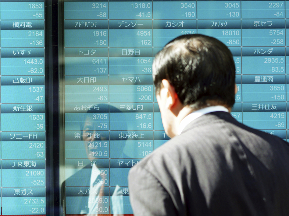 A man looks at an electronic stock board showing Japan's Nikkei 225 index on Thursday in Tokyo. (Eugene Hoshiko/AP)