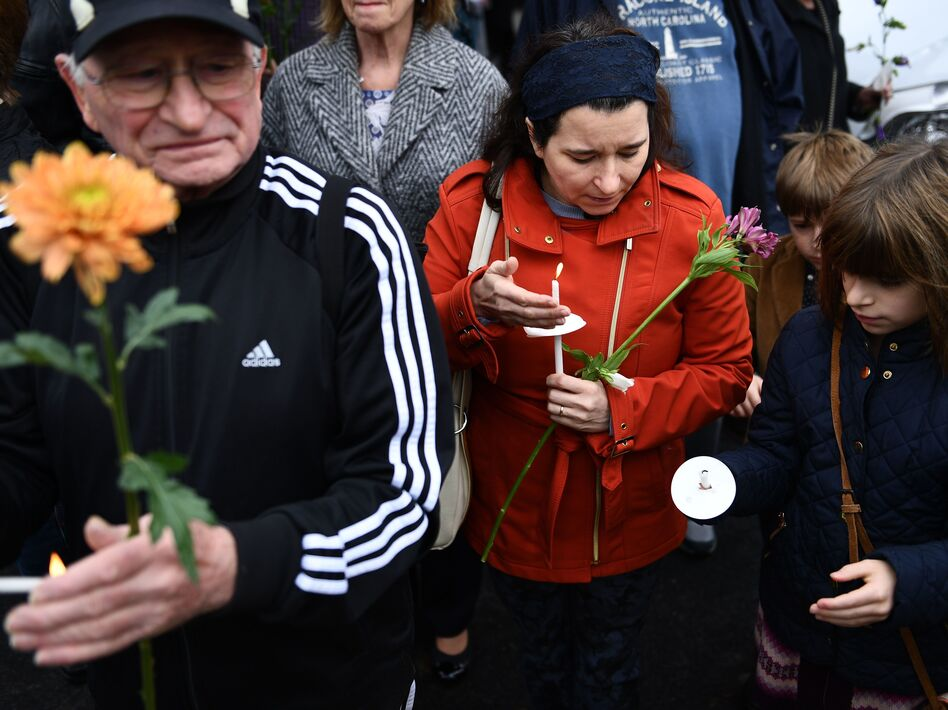 People pay their respects outside the Tree of Life synagogue in Pittsburgh. The 11 people who were killed on Saturday ranged in age from 54 to 97. (Brendan Smialowski/AFP/Getty Images)
