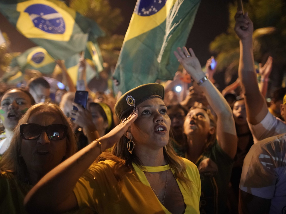 A supporter of Jair Bolsonaro salutes during a celebration in front of his residence after he was declared the winner of the election runoff, in Rio de Janeiro, on Sunday. (Leo Correa/AP)