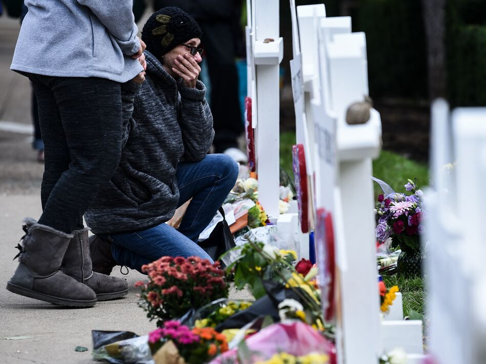 People pay their respects at a memorial outside the Tree of Life synagogue in Pittsburgh after a shooting there left 11 people dead. Many people see a connection between President Trump's anti-immigrant rhetoric and hate crimes. (Brendan Smialowski/AFP/Getty Images)