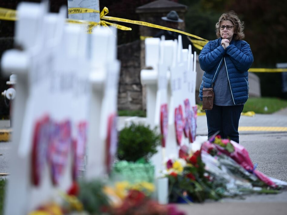 A woman prays before a memorial outside the Tree of Life synagogue after a shooting there left 11 people dead in Pittsburgh on Saturday. (Brendan Smialowski/AFP/Getty Images)
