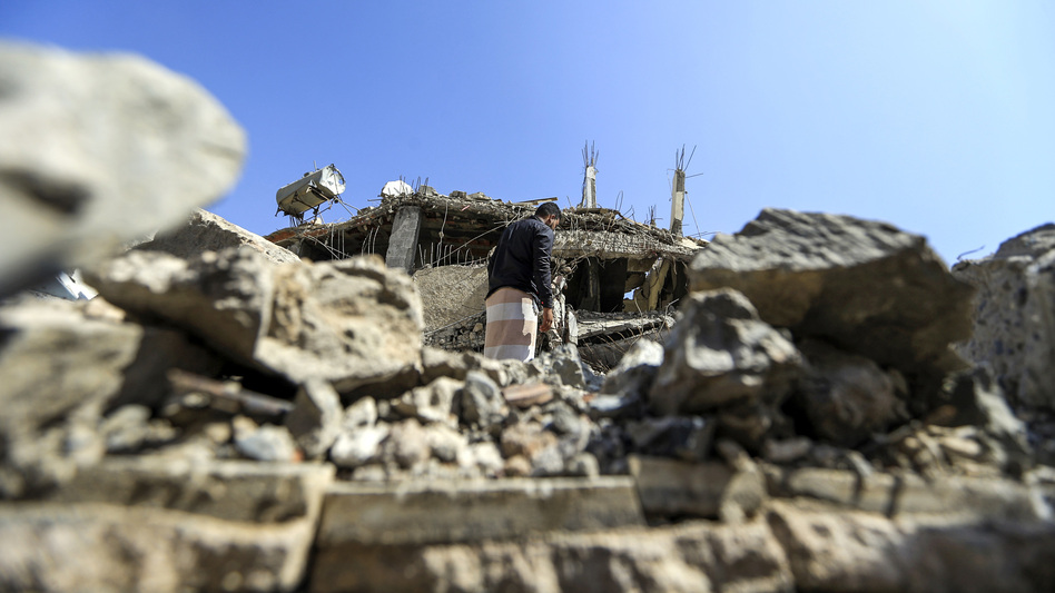 """A Yemeni man walks through the rubble of a building after a Saudi-led coalition airstrike last month in the capital, Sanaa. """"The time is now for the cessation of hostilities,"""" U.S. Secretary of State Mike Pompeo said Tuesday. (Mohammed Huwais/AFP/Getty Images)"""