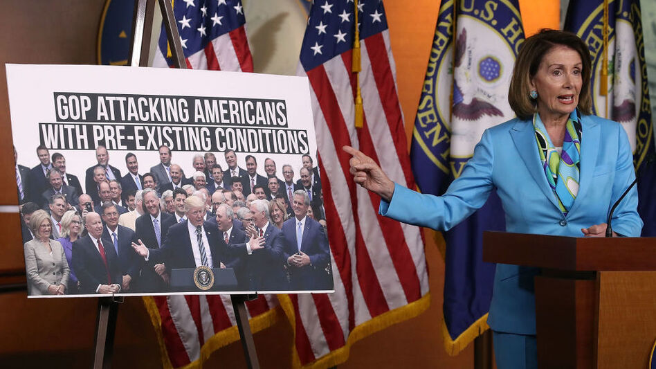 Democratic Minority Leader Nancy Pelosi, D-Calif., speaks about health care as she points to a picture of President Trump with House GOP members during her weekly news conference on Capitol Hill in June. (Mark Wilson/Getty Images)