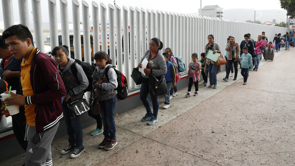 People line up to cross into the United States to begin the process of applying for asylum near the San Ysidro Port of Entry in Tijuana, Mexico. President Trump has threatened to close the border to asylum-seekers. (Gregory Bull/AP)