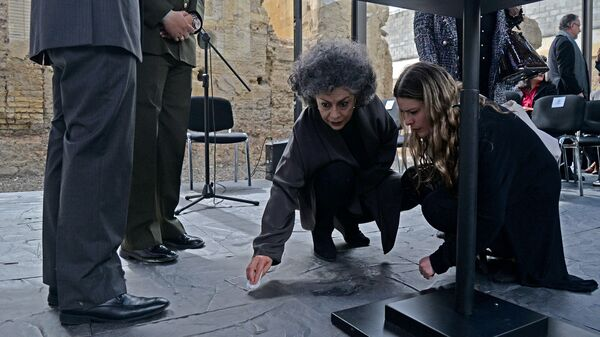 Colombian sculptor Doris Salcedo (center) cleans a spill on the floor during the pre-inauguration of her peace monument titled Fragmentos (Fragments), for which she used metal melted-down from the weapons handed over by FARC guerrilla fighters to make the floor, in Bogotá on July 31.