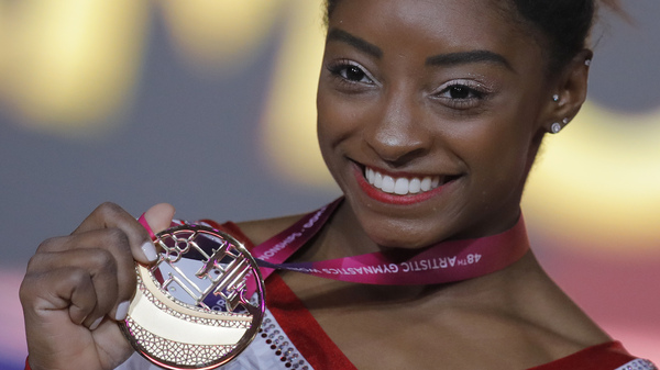 Simone Biles of the U.S. shows her gold medal after the women