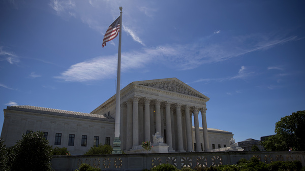 A flag flies outside the U.S. Supreme Court in June 2017. The Department of Justice has asked the court to intervene in pending cases about the legality of the Trump administration