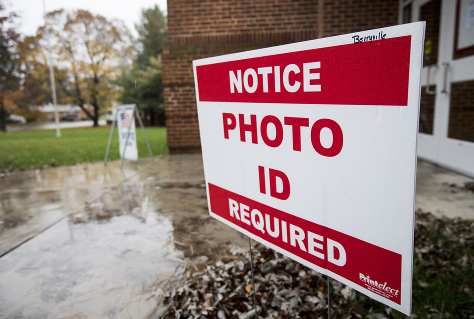 North Carolina will join Virginia and 17 other states that require voters to show a photo ID to vote. A sign notifies voters that a photo ID is required at the Clarke County Schools office polling location in Berryville, Va., on Nov. 6, 2018. (Bill Clark/CQ-Roll Call,Inc./Getty Images)